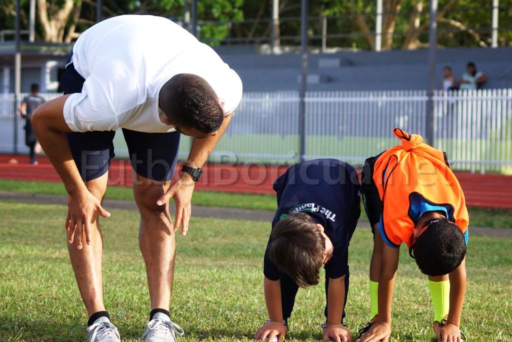 Tomás Flecha junto a dos de los niños participantes de las clínicas brindadas por Corazón Fútbol.