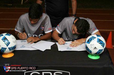 Kevin Hernández y Carlos Solá firmando los contratos con Assumption College. Suminsitrada
